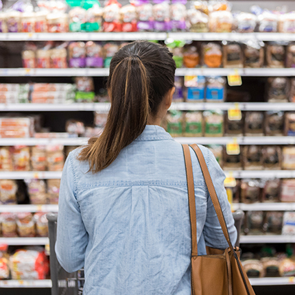 Woman standing in a grocery store isle infront of a shelve