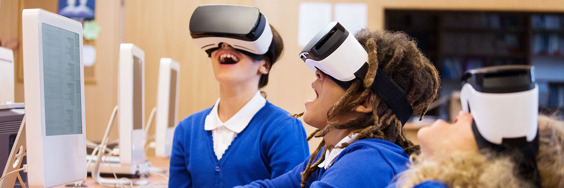 Kids playing with virtual reality headsets in a computer lab