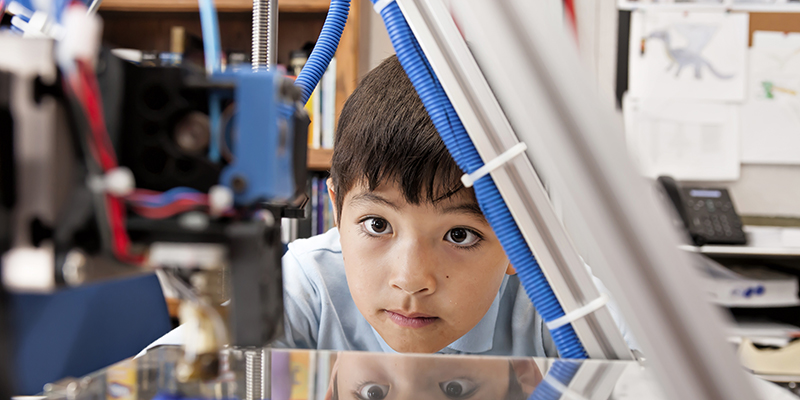 A young boy watching a 3D printing machine in progress
