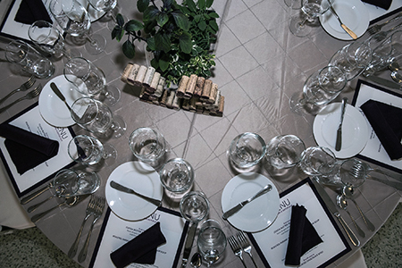 Birdseye view of an event table set with glasses and flatware