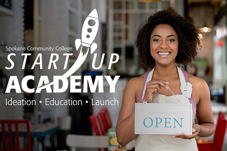 Spokane Community College Start Up Academy - African American woman standing in a cafe with an apron on holding an open sign